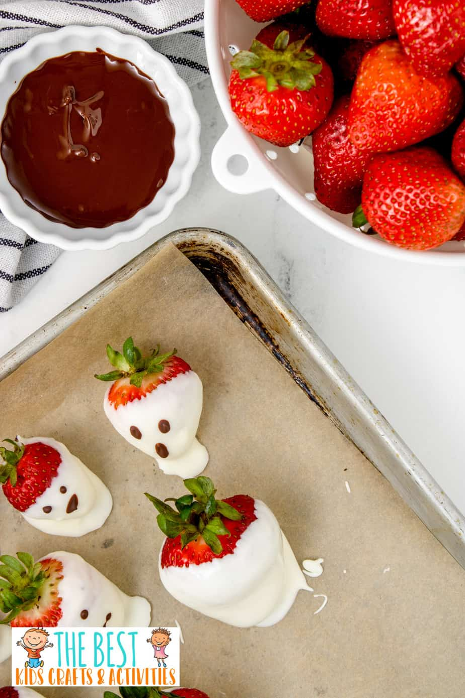 Halloween chocolate covered strawberries setting on a baking sheet